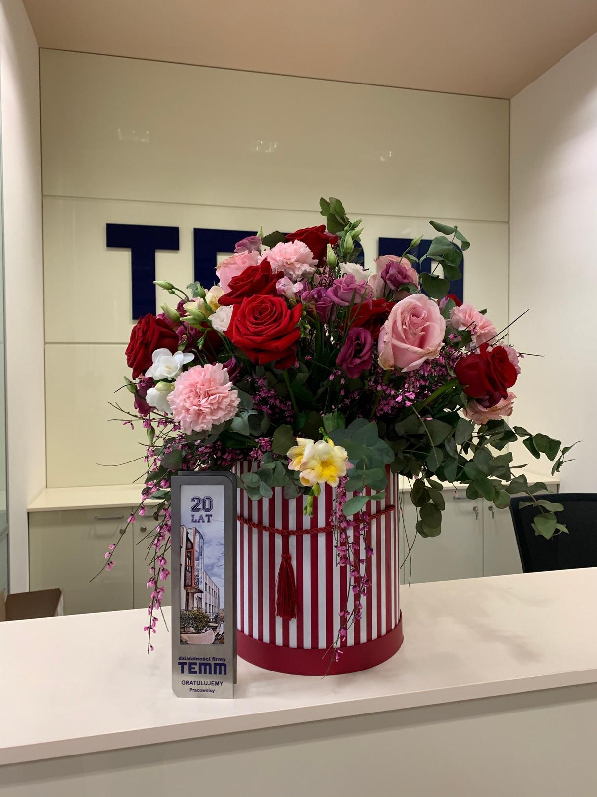 Zdjęcie bukietu kwiatów i statuetki to prezent od pracowników